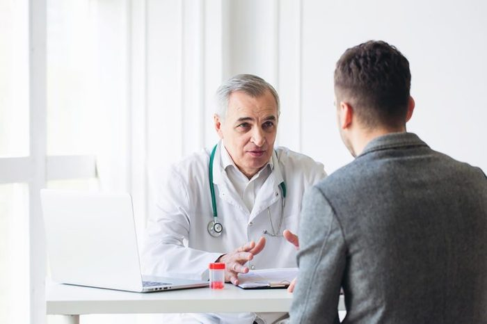 Elderly doctor explaining diagnosis to a young male patient