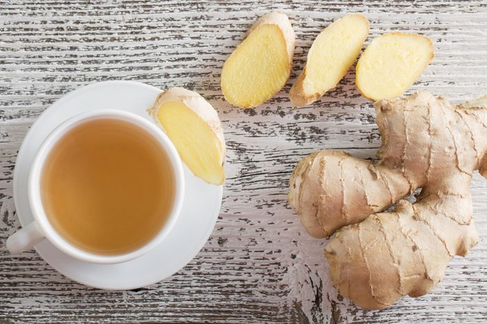 Ginger root, slices, and ginger tea in a white teacup