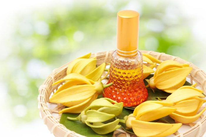 ylang ylang oil in a bottle surrounded by flowers on shallow basket