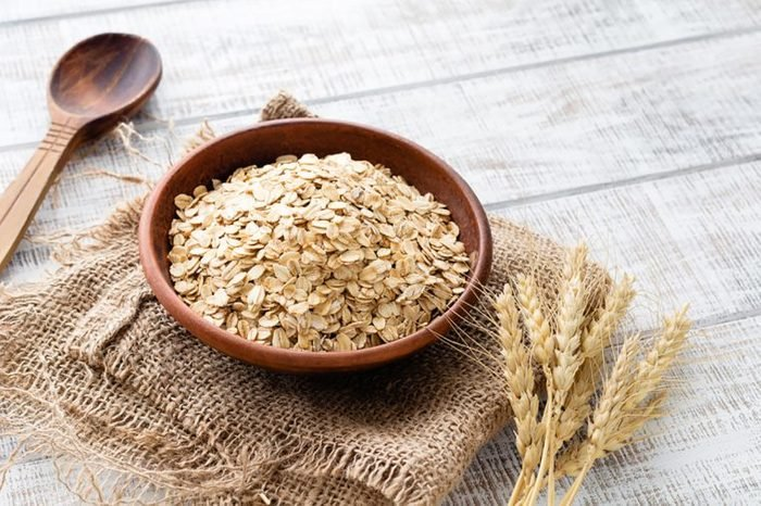 dry oats in a wooden bowl on a folded burlap sack