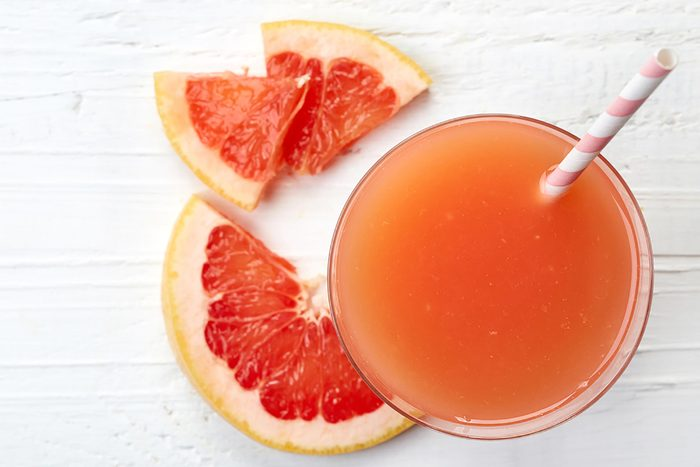 glass of grapefruit juice with a pink and white striped straw