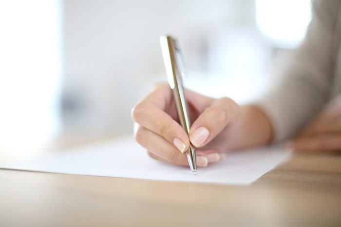 person writing with pen and paper