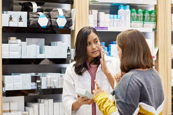 chemist explaining skin care product to customer