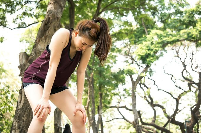 woman in workout gear outdoors, breathing heavily, hands on knees