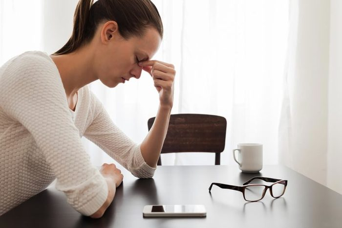 Stressed woman pinching the bridge of her nose with her fingers.