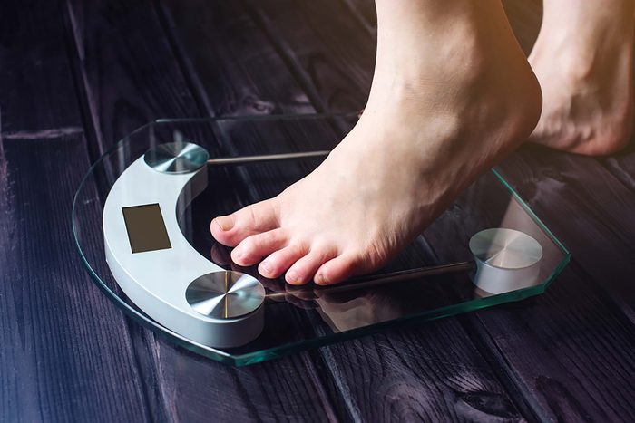 person stepping onto a digital scale