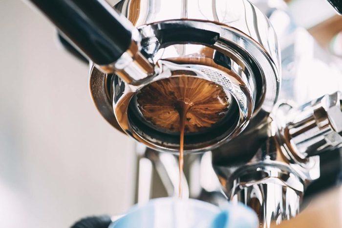 An espresso cup and espresso machine.
