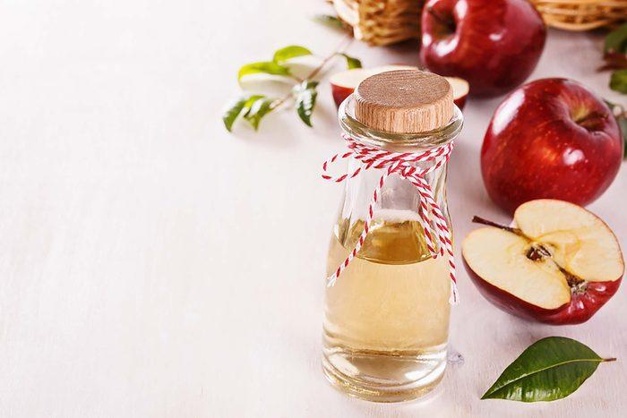 glass bottle of Apple cider vinegar with apples in background