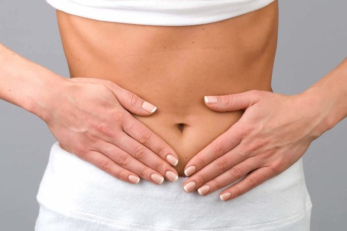 Woman with hands on bare stomach