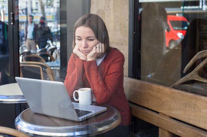 woman at computer looking sad