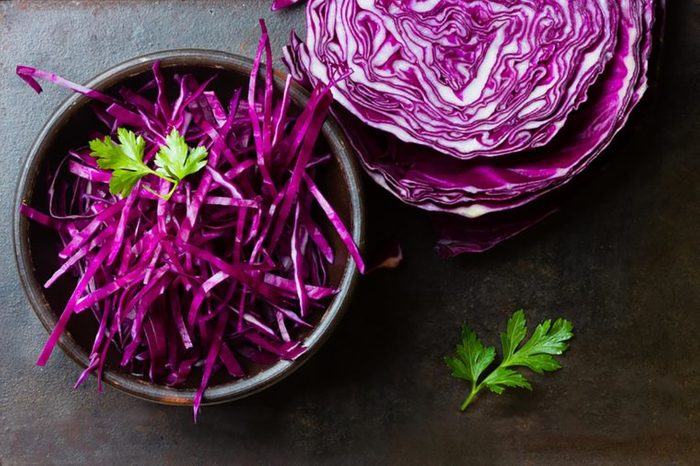 shredded purple cabbage in bowl and half the head