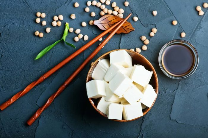 cubed tofu in a bowl with chopsticks and soy sauce