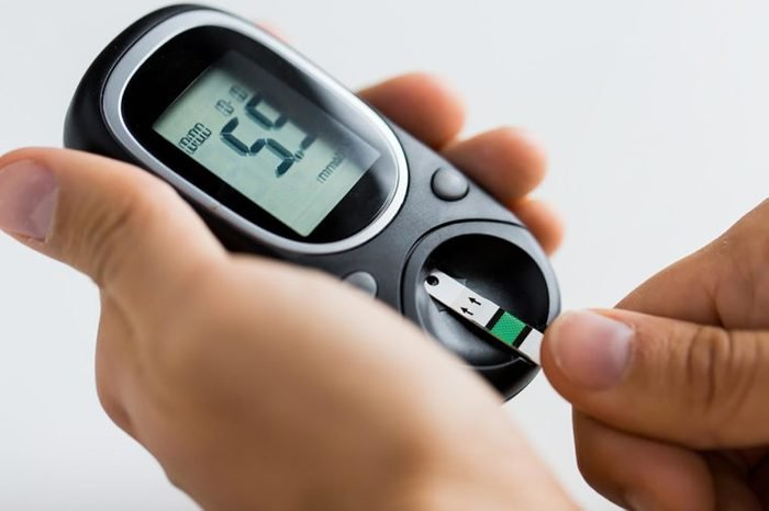 Person checking their blood sugar with a glucose monitor.