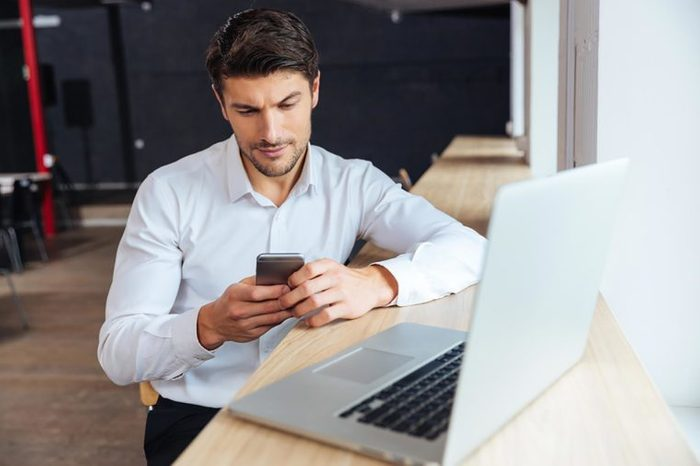 man checking his cellphone while at his computer