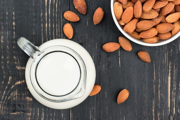 Bowl of almonds and a pitcher of milk on a table.
