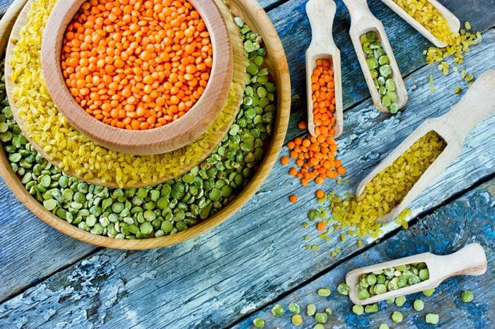 bowls of red, yellow, and green lentils with scoops