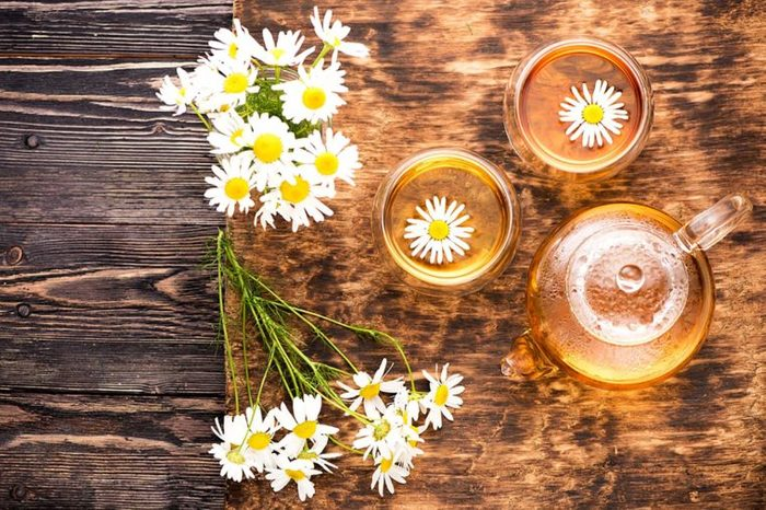 Chamomile blossoms on a table and floating in tea