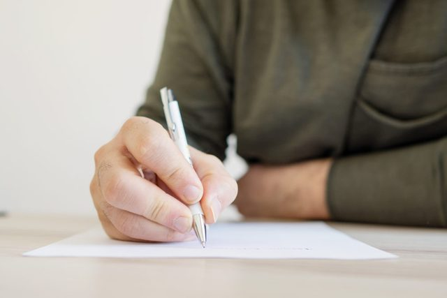 close up of man writing on paper