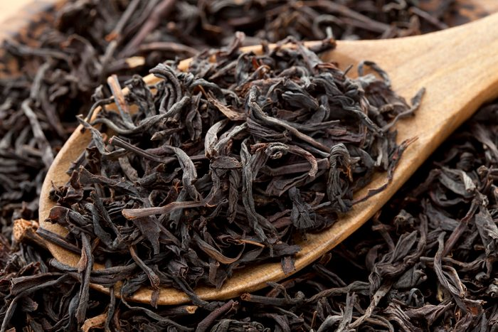 dry black tea in wooden spoon close up