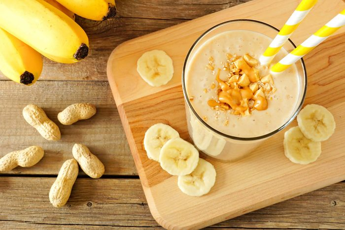 smoothie in a tall glass surrounded by banana slices, bananas, and peanuts in the shell