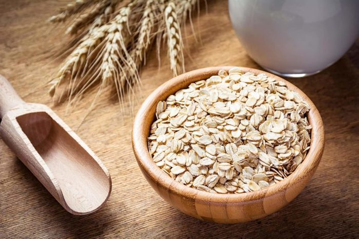 Bowl of raw oats and a wooden scoop