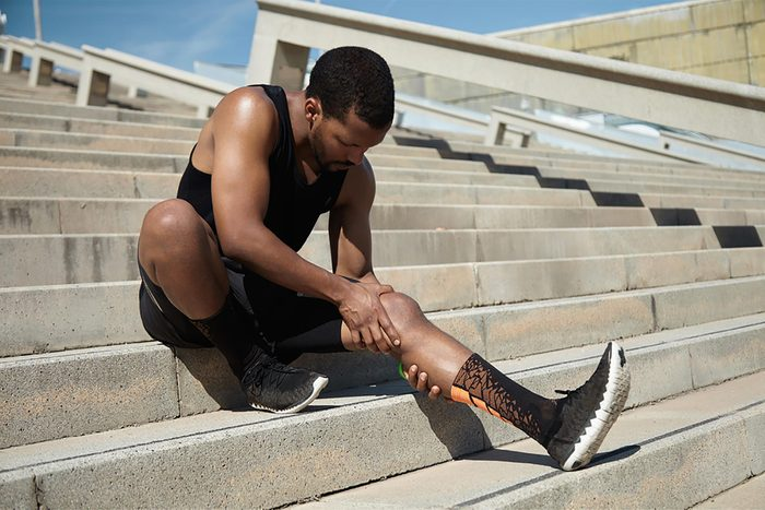 African-American man in workout gear clutching his left calf