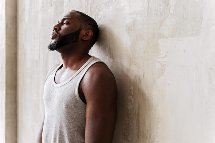 tired man in tank top leaning against wall
