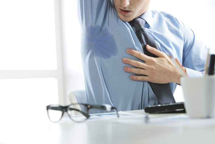 Man at desk checking out a sweat mark on his shirt.