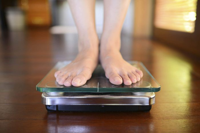 Closeup of someone's feet on a scale.