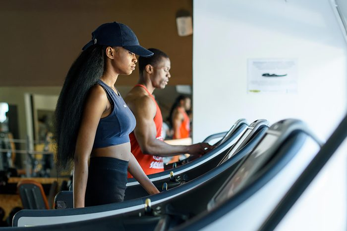 Woman in a baseball cap walking on a treadmill at the gym.