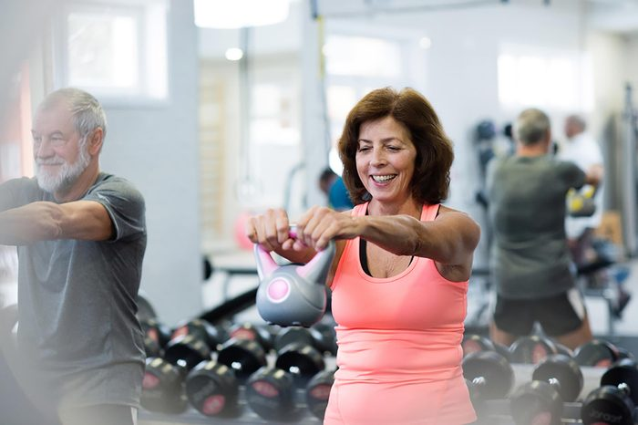 middle-aged man and woman lifting a kettle bell