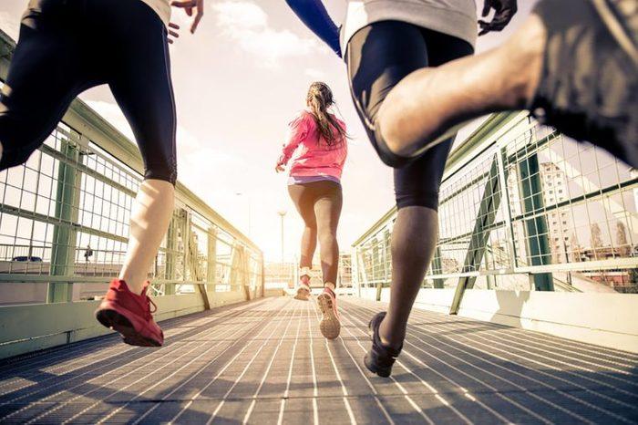 People running on a pedestrian bridge