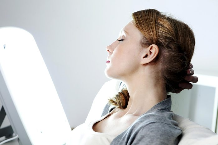 Woman with eyes closed receiving light therapy