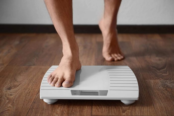 person stepping onto scale