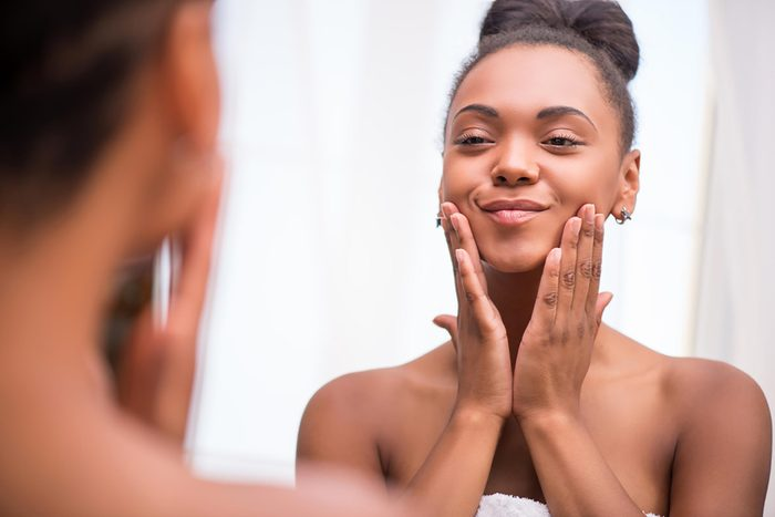 black woman smiling and examining her complexion in the mirror
