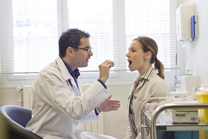doctor placing a tongue depressor in a woman's mouth