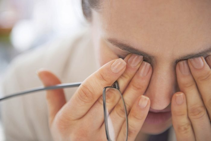 Woman with tilted head presses her fingers against her tired eyes.