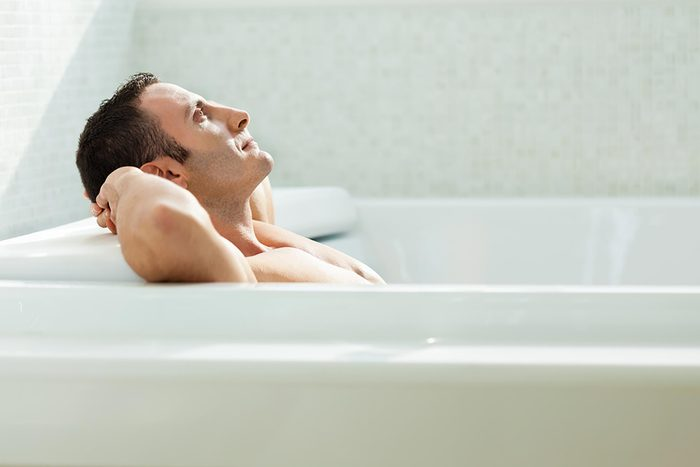 man soaking in tub with hands behind his head