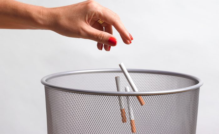 throwing cigarettes into garbage can
