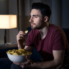man eating chips while watching a movie at home