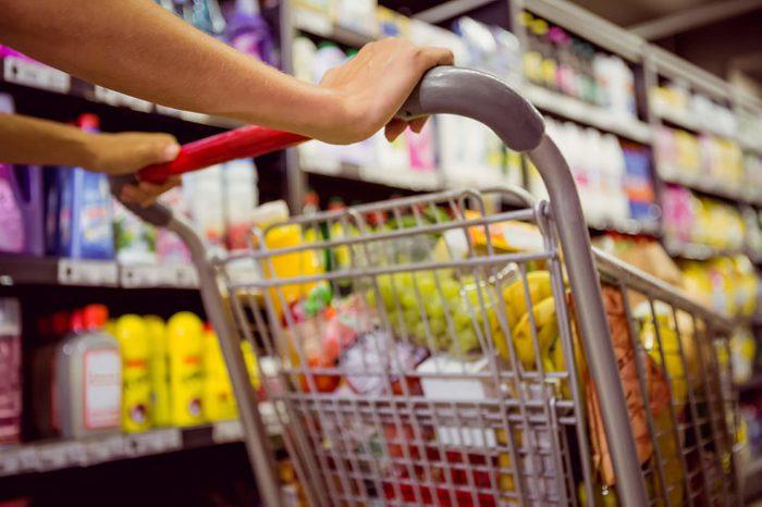 woman pushing shopping cart in grocery store