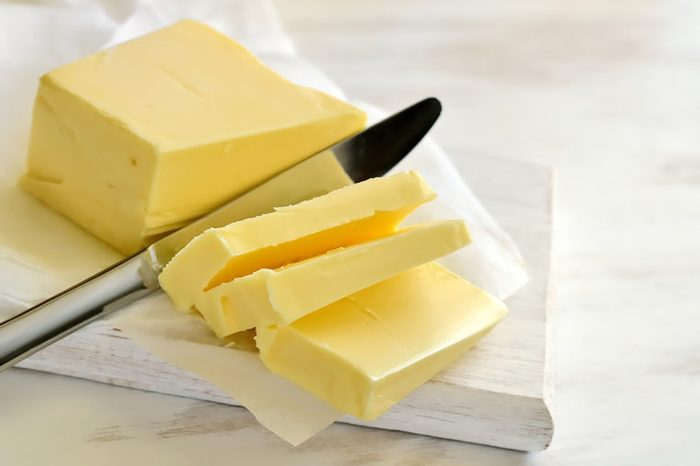 knife slicing butter on a white board