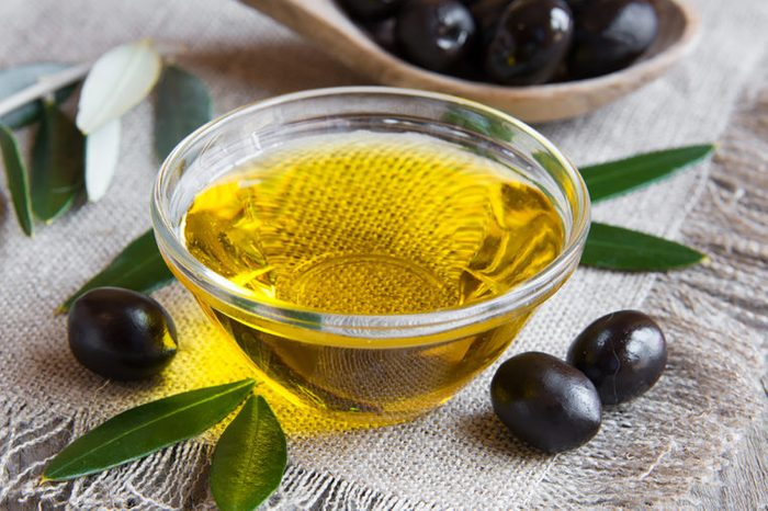 Olive-oil in a bowl with black olives on the side