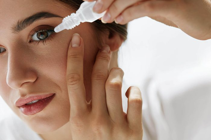 woman putting drops in her eyes