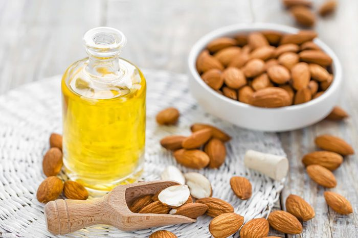 Almond-oil in a jar with bowl of almonds and scattered almonds