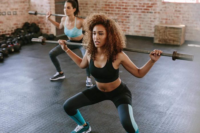 Young exercising with barbell in fitness class