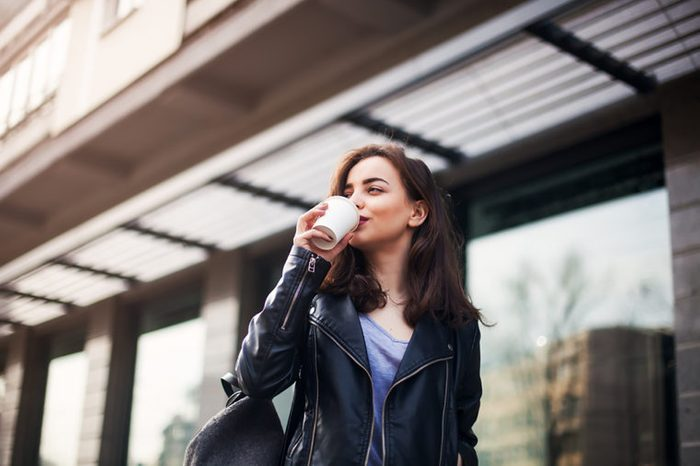 woman walking and drinking coffee
