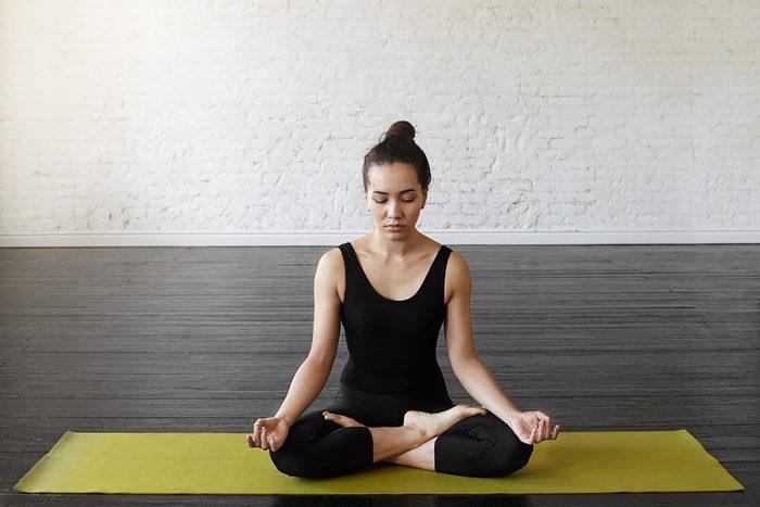 woman doing meditation exercise on mat