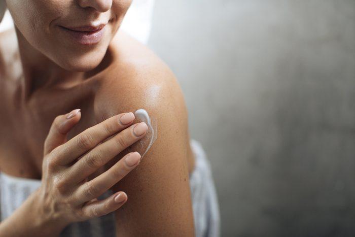 woman putting moisturizer on her shoulder