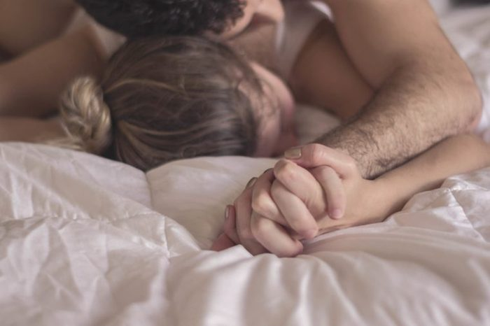 Man and woman in bed together holding hands.